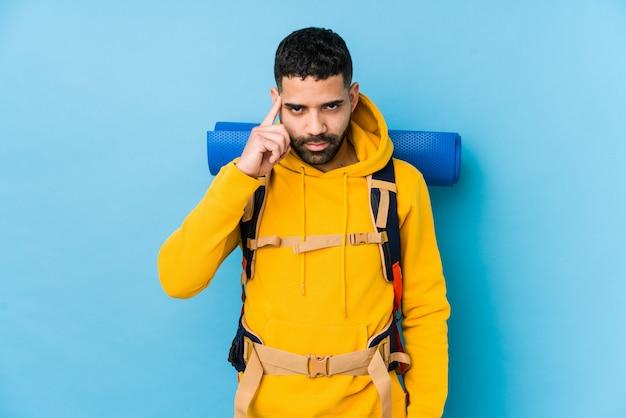 Młody podróżnik arabski backpacker mężczyzna na białym tle wskazując świątynię palcem, myślenia, koncentruje się na zadaniu.