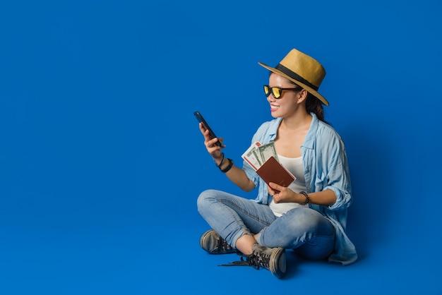 Młody podróżnik azjatycki szczęśliwy w niebieskiej koszuli, trzymając paszport z trzymając telefony komórkowe w dłoni. koncepcja podró?y ze sprz?tem dla podró?nych wakacje, na tle koloru niebieskiego. relaks w podróży