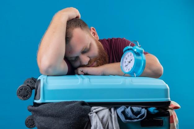 Młody podróżnik brodaty opierając głowę na walizce pełnej ubrań z budzikiem na nim śpi