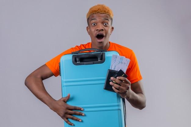 Młody podróżnik chłopiec ubrany w pomarańczową koszulkę, trzymając walizkę i bilety lotnicze, zaskoczony i zdumiony szczęśliwy stojąc nad białą ścianą