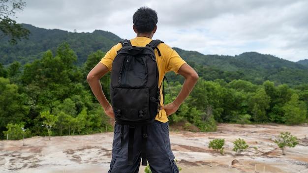 Młody podróżnik człowiek z plecakiem stojący zrelaksować się na tle krajobrazu górskiego szczytu w phuket, tajlandia
