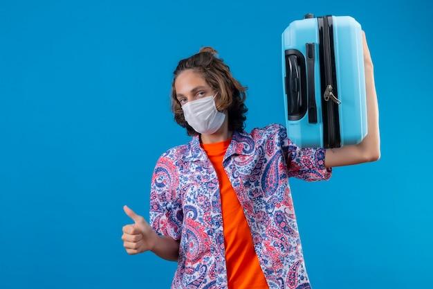 Młody podróżnik facet ubrany w maskę ochronną na twarz, trzymając walizkę podróżną, patrząc pewnie, pokazując kciuki stojąc na niebieskim tle