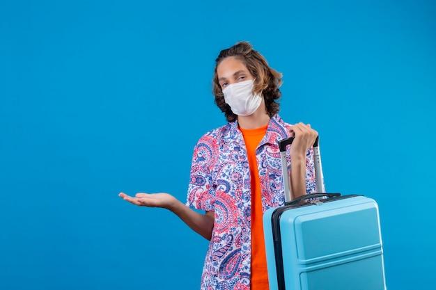 Młody podróżnik facet ubrany w maskę ochronną, trzymając walizkę podróżną, nieświadomy i zdezorientowany, stojąc z ręką uniesioną na niebieskim tle