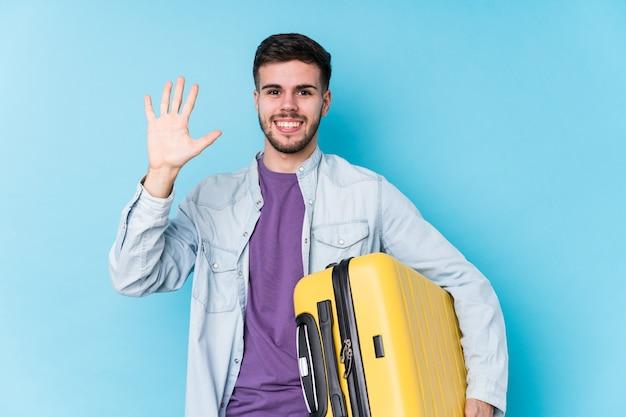 Młody podróżnik kaukaski mężczyzna trzyma walizkę na białym tle uśmiechnięty wesoły pokazując numer pięć palcami.