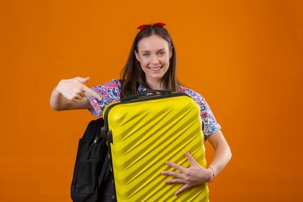 Młody podróżnik kobieta nosi czerwone okulary na głowie z plecakiem trzymając walizkę