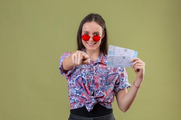 Młody podróżnik kobieta nosi czerwone okulary przeciwsłoneczne trzymając bilety uśmiechając się z szczęśliwą twarzą, wskazując palcem na aparat stojący na zielonym tle