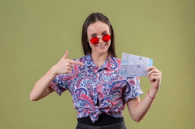 Młody podróżnik kobieta nosi czerwone okulary przeciwsłoneczne trzymając bilety wskazując palcem do nich, uśmiechając się z radosną twarzą stojącą na zielonym tle