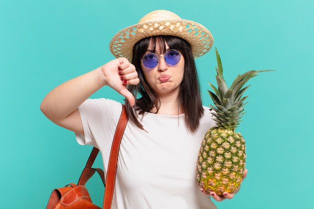 Młody podróżnik kobieta smutny wyraz i trzyma ananas