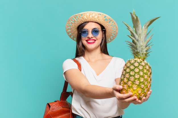 Młody podróżnik kobieta szczęśliwy wyraz i trzyma ananas