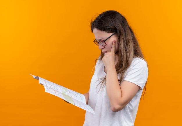 Młody podróżnik kobieta w białej koszulce trzymając mapę patrząc na to z zamyślonym wyrazem twarzy myślenia stojącego nad pomarańczową ścianą