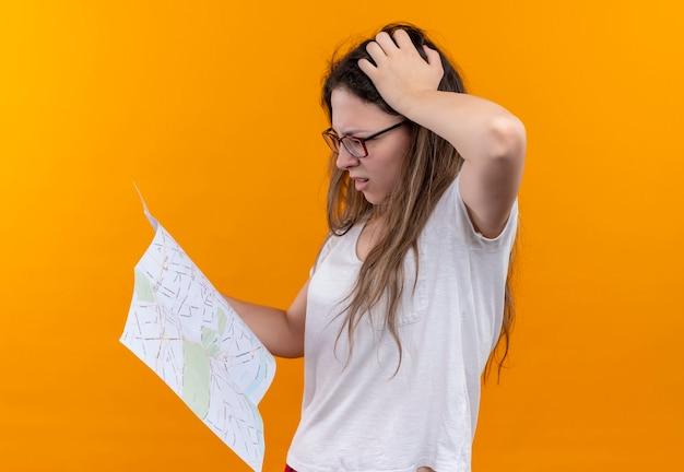 Młody podróżnik kobieta w białej koszulce trzymając mapę patrząc na to z zamyślonym wyrazem twarzy patrząc zdezorientowany stojąc nad pomarańczową ścianą