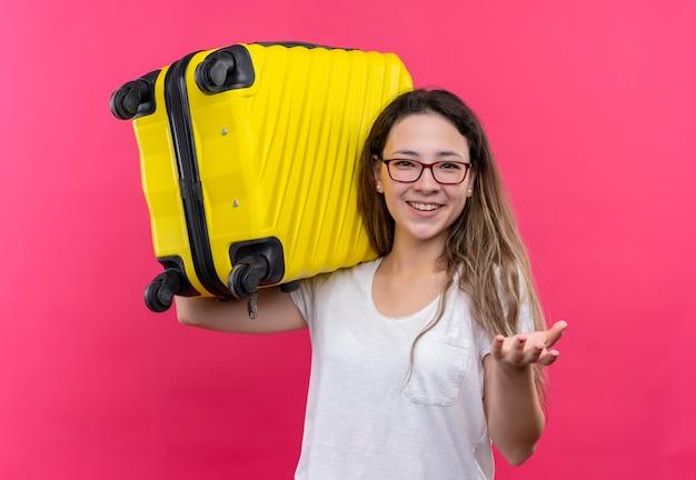Młody podróżnik kobieta w białej koszulce trzymając walizkę podróżną, uśmiechając się radośnie podnosząc rękę stojącą nad różową ścianą
