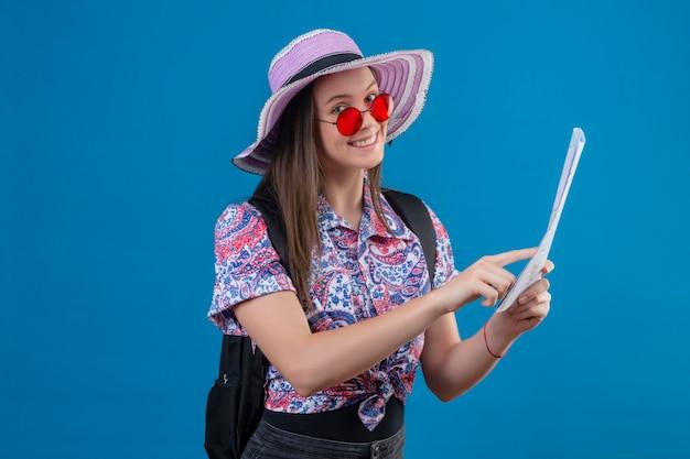 Młody podróżnik kobieta w kapeluszu lato na sobie czerwone okulary przeciwsłoneczne trzyma mapę wskazując palcem na to uśmiechnięty wesoło stojąc na niebieskim tle