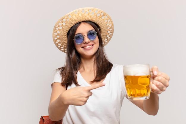 Młody podróżnik kobieta wskazuje lub pokazuje i trzyma piwo