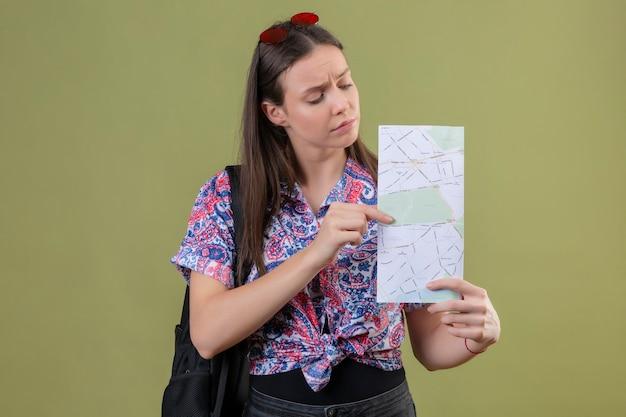 Młody podróżnik kobieta z czerwonymi okularami przeciwsłonecznymi na głowie iz plecakiem trzymając mapę patrząc na to z poważną twarzą stojącą na zielonym tle