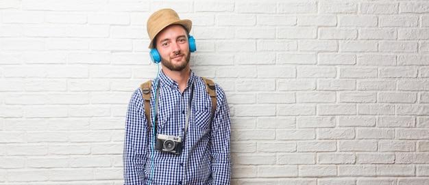 Młody podróżnik mężczyzna jest ubranym plecaka i rocznik kamerę pogodną iz dużym uśmiechem co