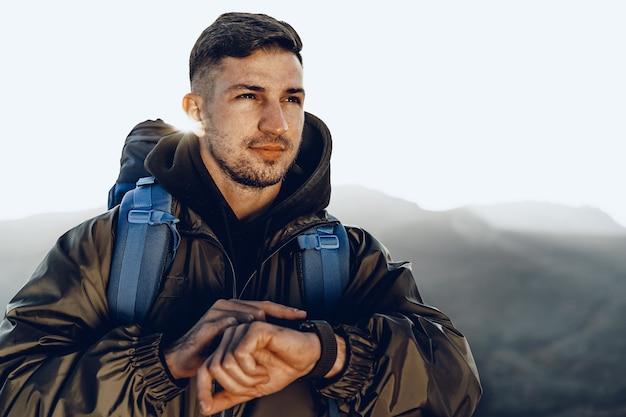 Młody podróżnik mężczyzna patrząc na jego inteligentny zegarek
