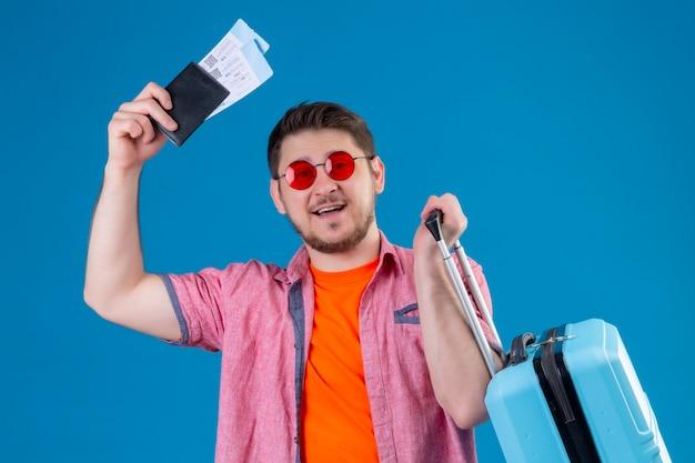 Młody podróżnik mężczyzna posiadający bilety lotnicze i walizkę patrząc na kamery uśmiechnięty z szczęśliwą twarzą stojącą na na białym tle niebieskim tle
