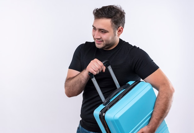 Młody podróżnik mężczyzna w czarnej koszulce trzyma walizkę patrząc na bok pozytywny i szczęśliwy uśmiechnięty stojący nad białą ścianą