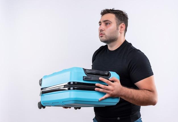 Młody podróżnik mężczyzna w czarnej koszulce trzyma walizkę patrząc na bok z poważnym wyrazem twarzy stojącej na białej ścianie