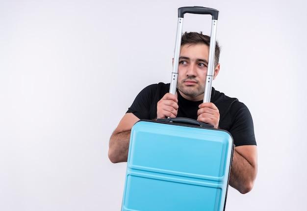 Młody podróżnik mężczyzna w czarnej koszulce trzyma walizkę patrząc na bok zmartwiony wyrazem strachu stojącym nad białą ścianą