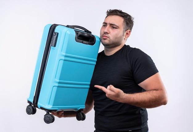 Młody podróżnik mężczyzna w czarnej koszulce trzyma walizkę wskazując palcem na to, patrząc niepewnie i zdezorientowany stojąc nad białą ścianą