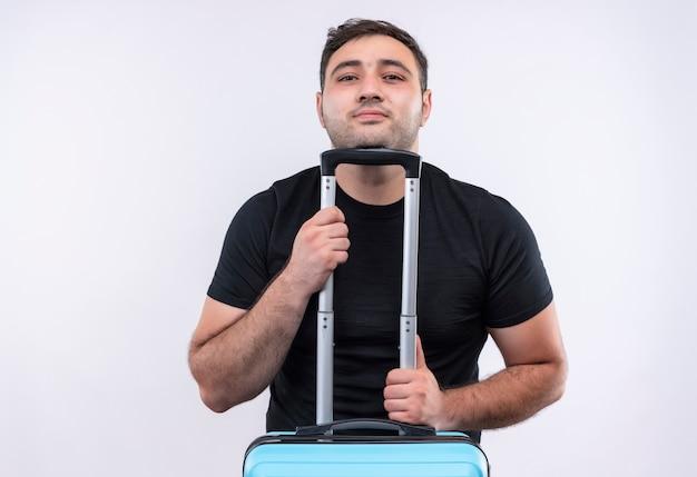 Młody podróżnik mężczyzna w czarnej koszulce trzyma walizkę z pewnym uśmiechem na twarzy stojącej nad białą ścianą