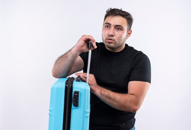 Młody podróżnik mężczyzna w czarnej koszulce trzymający walizkę patrząc na bok zdziwiony stojąc nad białą ścianą