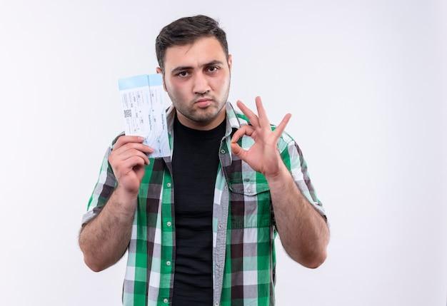 Młody podróżnik mężczyzna w koszuli w kratkę, posiadający bilety lotnicze, pewny siebie, robiący znak ok stojąc nad białą ścianą