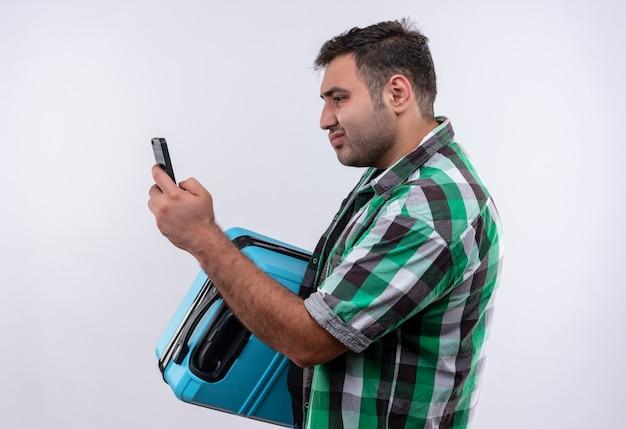 Młody podróżnik mężczyzna w kraciastej koszuli stojący z walizką, patrząc na ekran swojego smartfona, patrząc zdezorientowany na białej ścianie