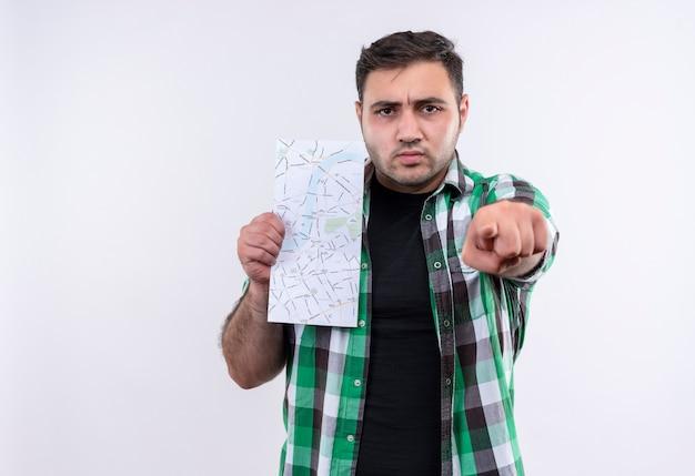 Młody podróżnik mężczyzna w kraciastej koszuli trzymając mapę wskazując palcem na aparat z marszczoną twarzą stojącą nad białą ścianą