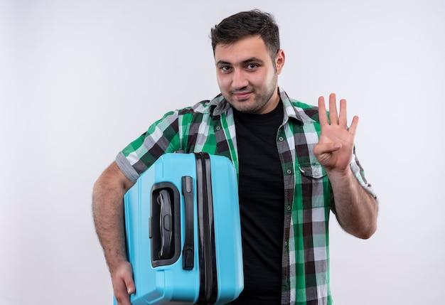 Młody podróżnik mężczyzna w kraciastej koszuli, trzymając walizkę, uśmiechając się, pokazując i wskazując palcami numer cztery stojąc na białej ścianie