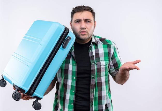 Młody podróżnik mężczyzna w kraciastej koszuli, trzymając walizkę zdezorientowany i niepewny, gestykuluje ręką stojącą nad białą ścianą