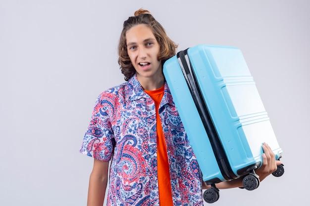 Młody podróżnik mężczyzna z niebieską walizką wyglądający pewnie, uśmiechnięty z szczęśliwą twarzą gotowy do podróży na stojąco