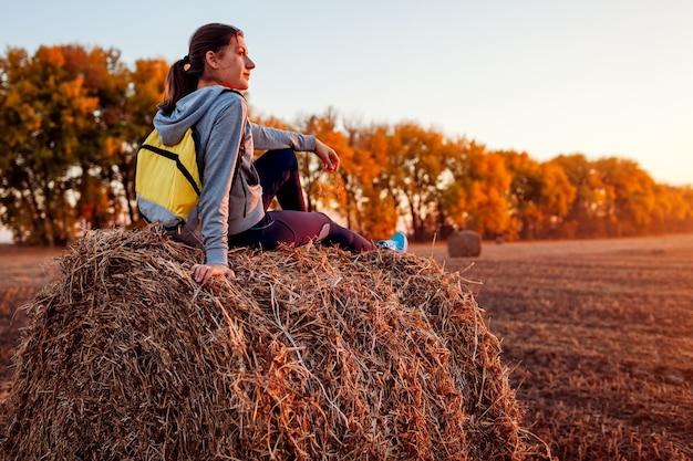 Młody podróżnik po odpoczynku w jesiennym polu o zachodzie słońca. kobieta podziwia widok siedząc na stogu siana. koncepcja rekreacji sportowej