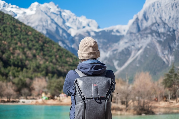 Młody podróżnik podróżujący w dolinie blue moon, charakterystycznym i popularnym miejscu w jade dragon snow mountain mountain scenic area, niedaleko lijiang old town. lijiang, yunnan, chiny. koncepcja podróży solo
