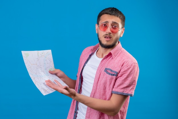 Młody podróżnik przystojny facet w okularach przeciwsłonecznych trzymając mapę patrząc na kamery z zmieszanym wyrazem twarzy stojącej na niebieskim tle