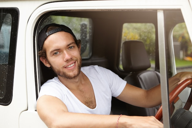 Młody podróżnik rasy kaukaskiej ubrany w casualowy t-shirt i czapkę z daszkiem, prowadzący swój biały samochód sportowy, cieszący się podróżą i wakacjami
