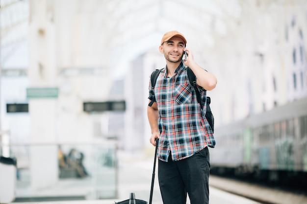 Młody podróżnik rozmawia przez telefon na stacji kolejowej
