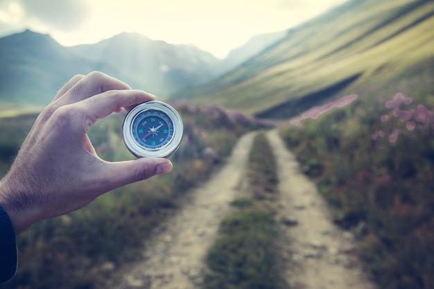 Młody podróżnik trzymając kompas w górach