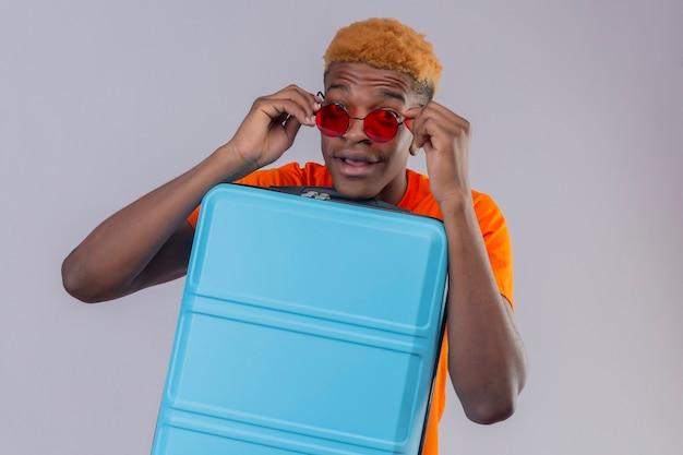 Młody podróżnik ubrany w pomarańczową koszulkę z walizką zaintrygowany zdjął okulary przeciwsłoneczne i stał na białej ścianie