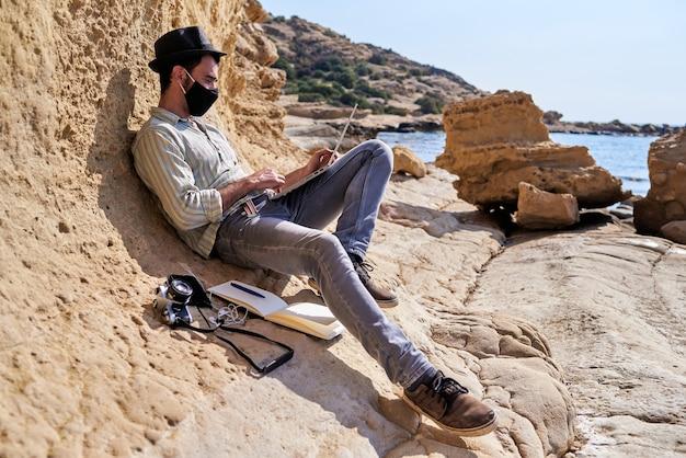 Młody podróżnik używa swojego laptopa do zdalnej pracy na świeżym powietrzu