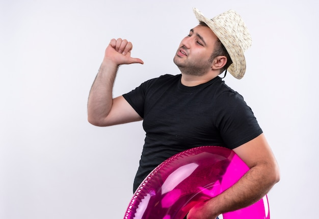 Młody podróżnik w czarnej koszulce i letnim kapeluszu trzymający nadmuchiwany pierścień wskazujący na siebie zadowolonego i dumnego stojącego nad białą ścianą