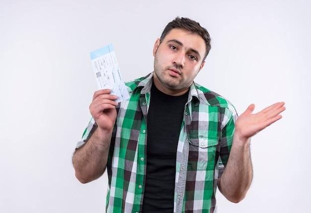Młody podróżnik w koszuli w kratkę, trzymający bilety lotnicze, wyglądający na zdezorientowanego i mającego wątpliwości stojąc nad białą ścianą