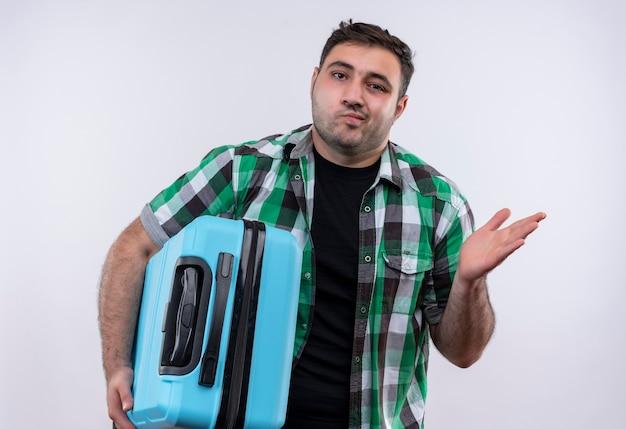 Młody podróżnik w kraciastej koszuli trzymający walizkę wyglądający na niepewnego i zdezorientowanego, rozkładający się z ręką na bok, bez odpowiedzi stojący nad białą ścianą