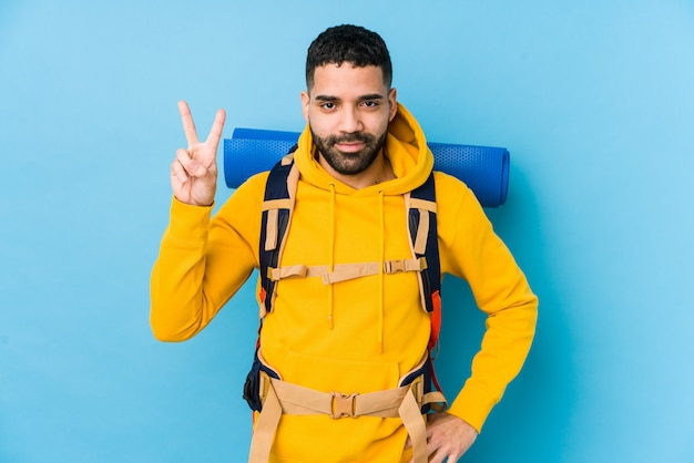 Młody podróżnika backpacker mężczyzna pokazuje numer dwa z palcami