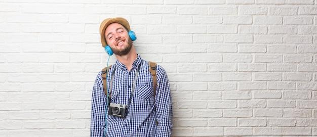 Młody podróżnika mężczyzna jest ubranym plecaka i rocznik kamerę rozochoconą iz dużym uśmiechem, ufnym, życzliwym i szczerym, wyrażający positivity i sukces.