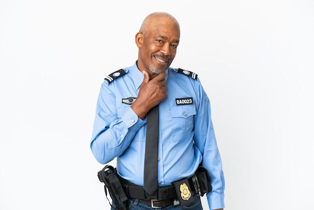Młody policjant na białym tle patrząc w bok i uśmiechnięty