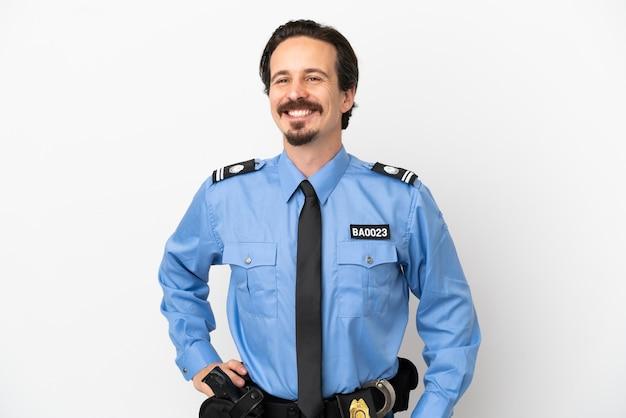 Młody policjant na białym tle, pozuje z rękami na biodrach i uśmiecha się