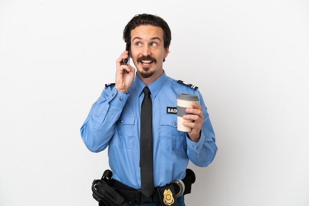 Młody policjant na białym tle trzyma kawę na wynos i telefon komórkowy